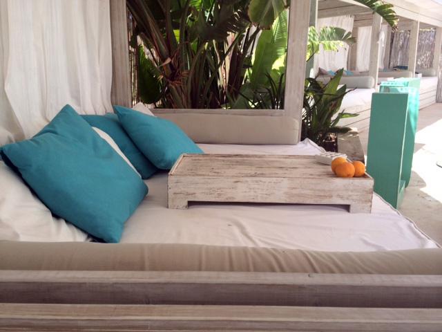 en la parte frontal del restaurante una composicin de mesas y sillas de color blanco decoradas con cojines de color azul turquesa y